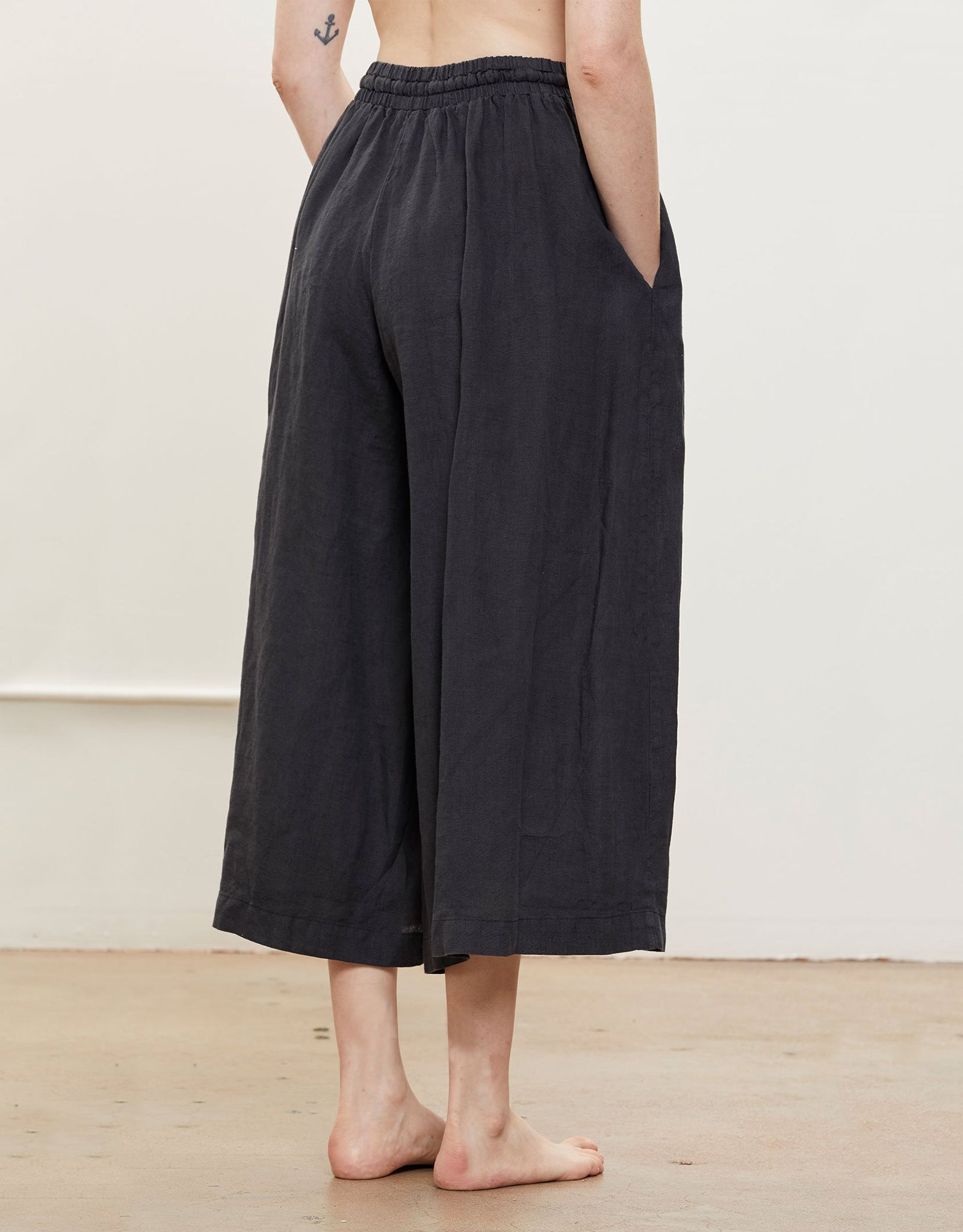 Model wears Black Crane Wide Culottes in Black, back. Available at FAWN Toronto.