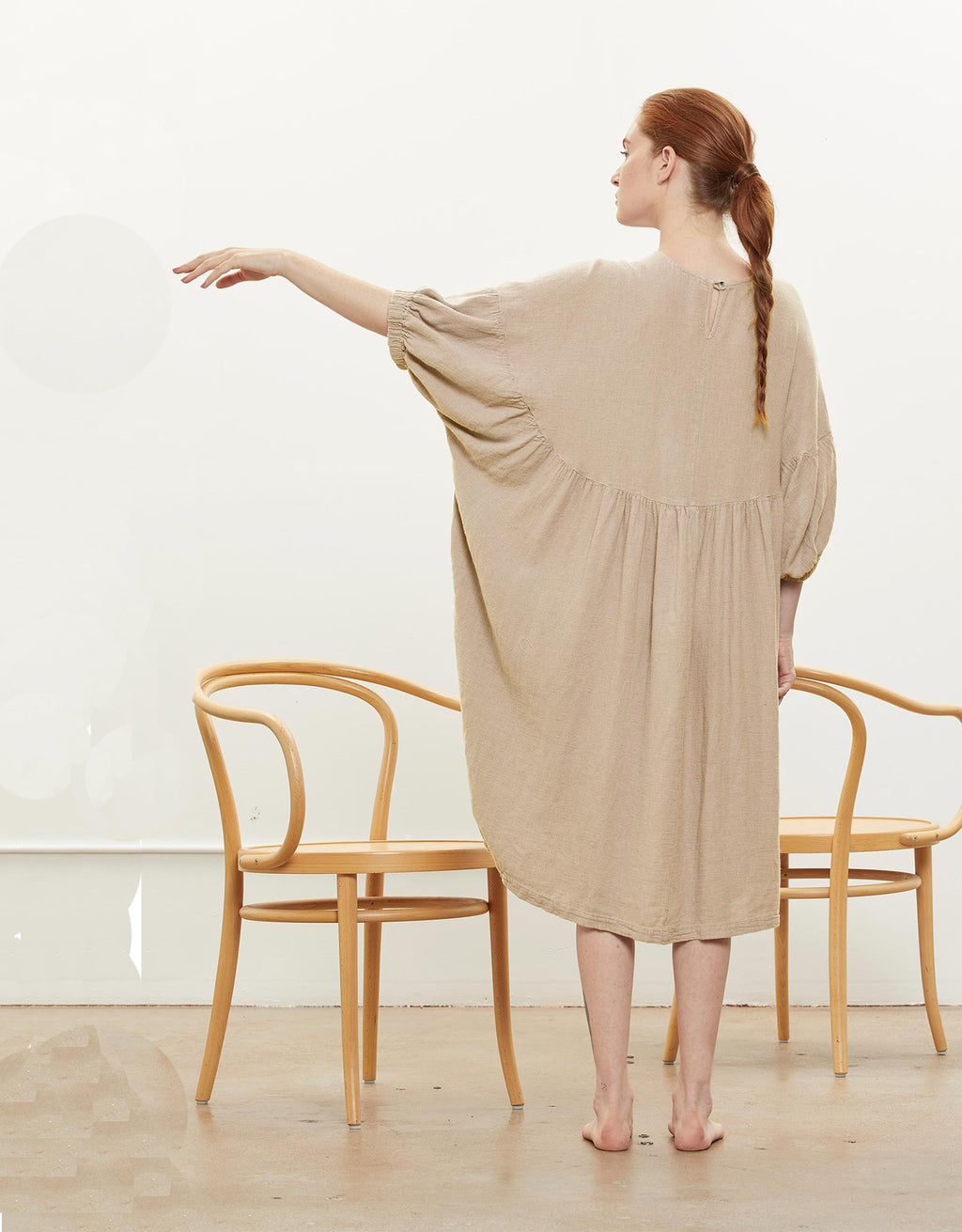 Model wears Black Crane Xiao Dress in Natural, back. Available at FAWN Toronto.