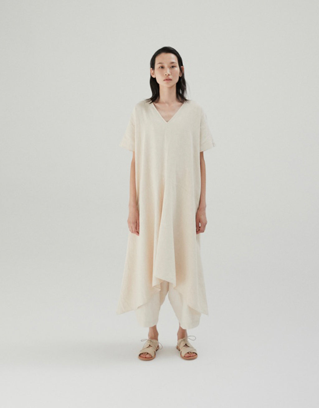 Model wears Monica Cordera Asymmetric Ramie Dress in Ivory. Available at FAWN Toronto.