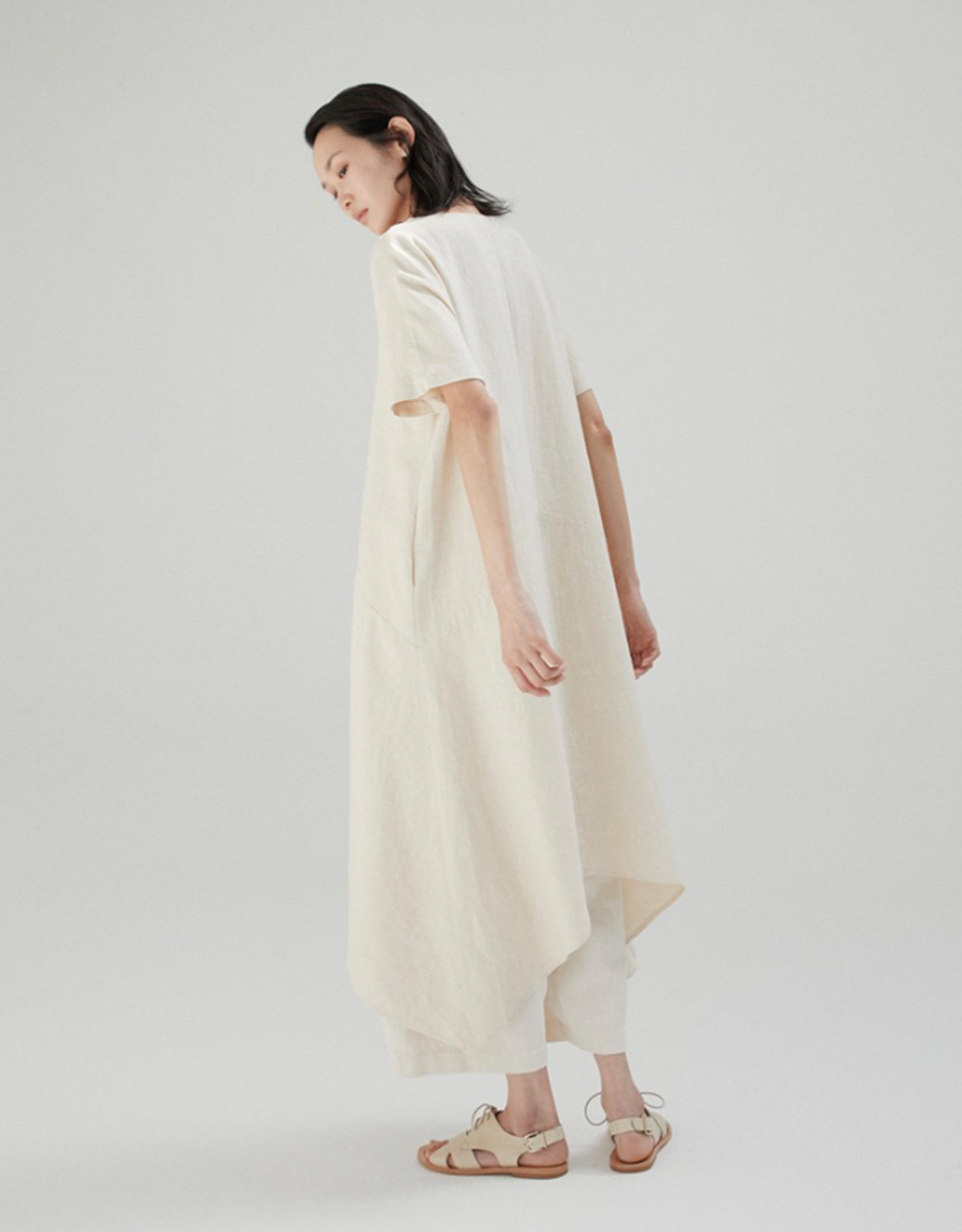 Model wears Monica Cordera Asymmetric Ramie Dress in Ivory, back. Available at FAWN Toronto.