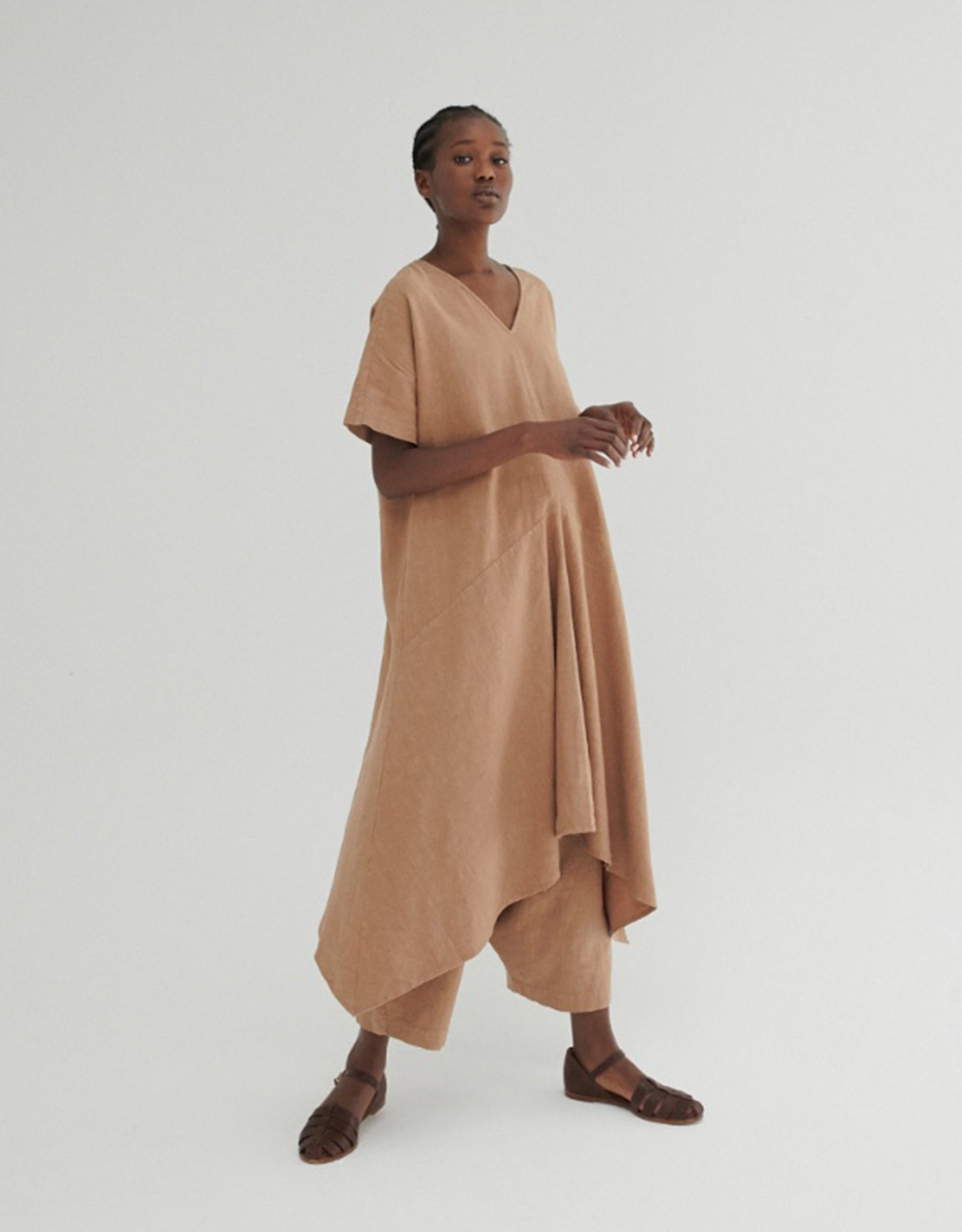 Model wears Monica Cordera Asymmetric Ramie Dress in tan. Available at FAWN Toronto.