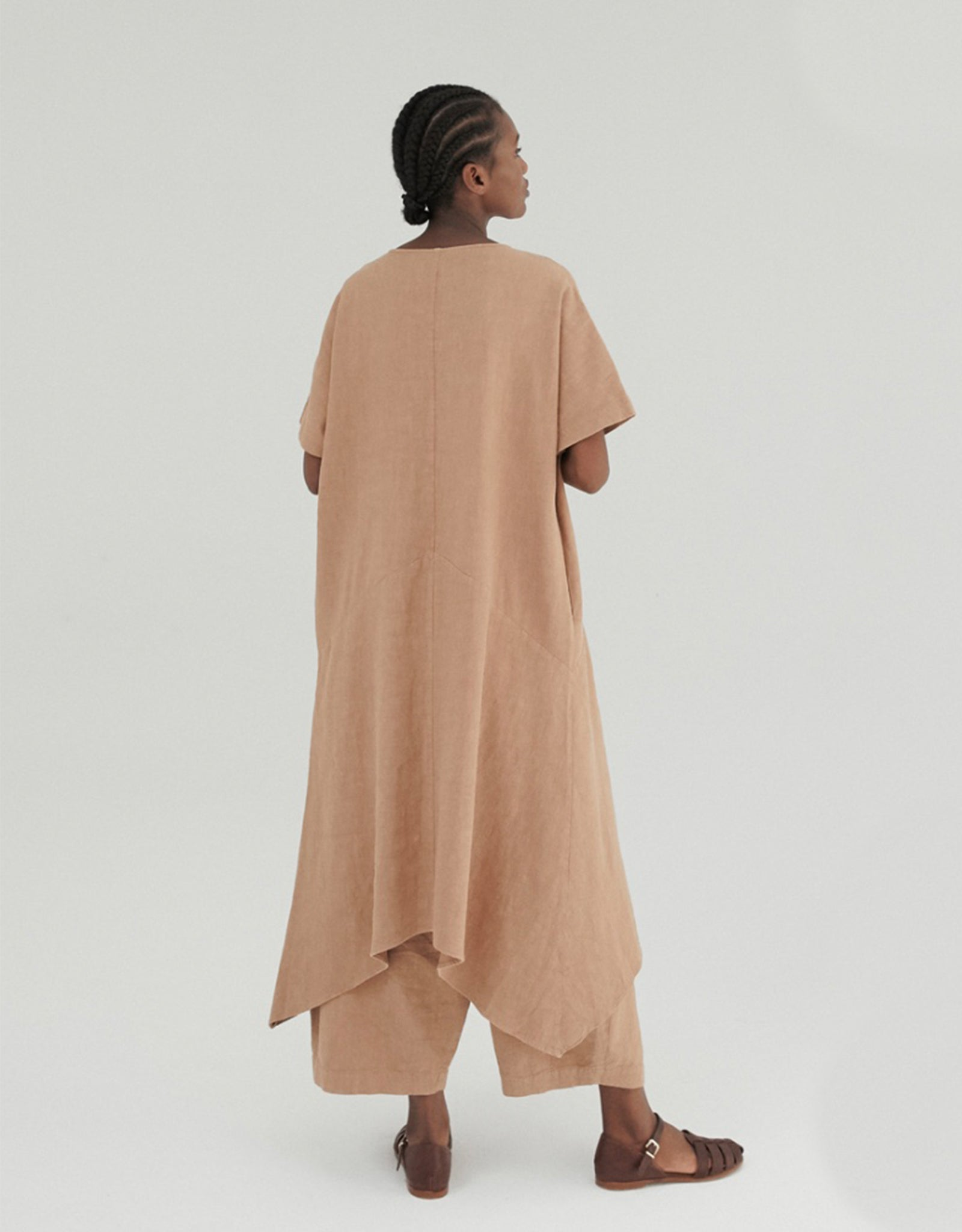Model wears Monica Cordera Asymmetric Ramie Dress in tan, back. Available at FAWN Toronto.