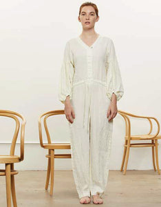 Model wears Black Crane Balloon sleeve jumpsuit in cream. Available at FAWN Toronto.