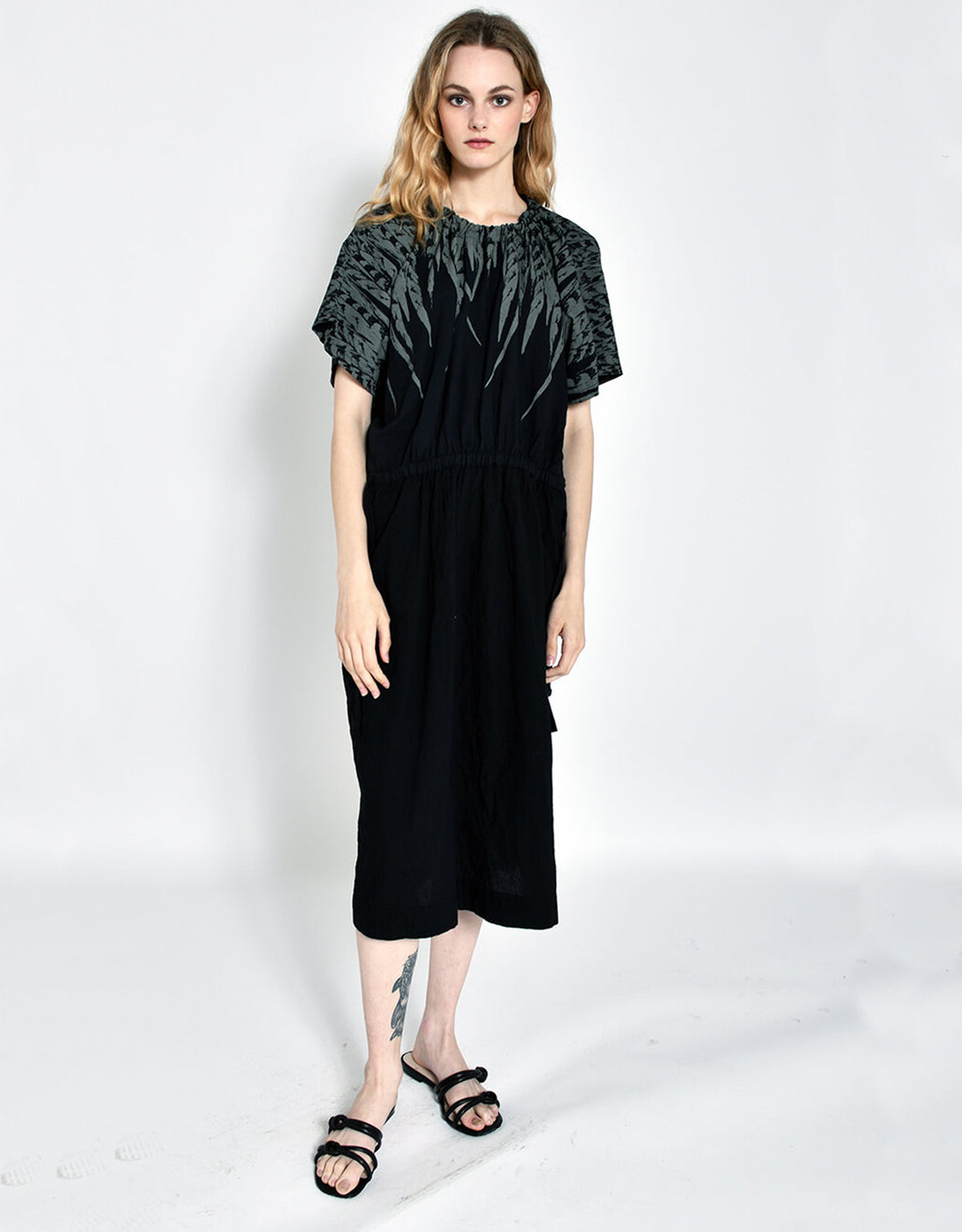 Model wears UZY NYC Earth Dress in Black with Grey feather detail. Available at FAWN Toronto.