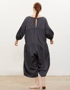 Model wears Black Crane Puff Jumpsuitin Faded Black, back. Available at FAWN Toronto.