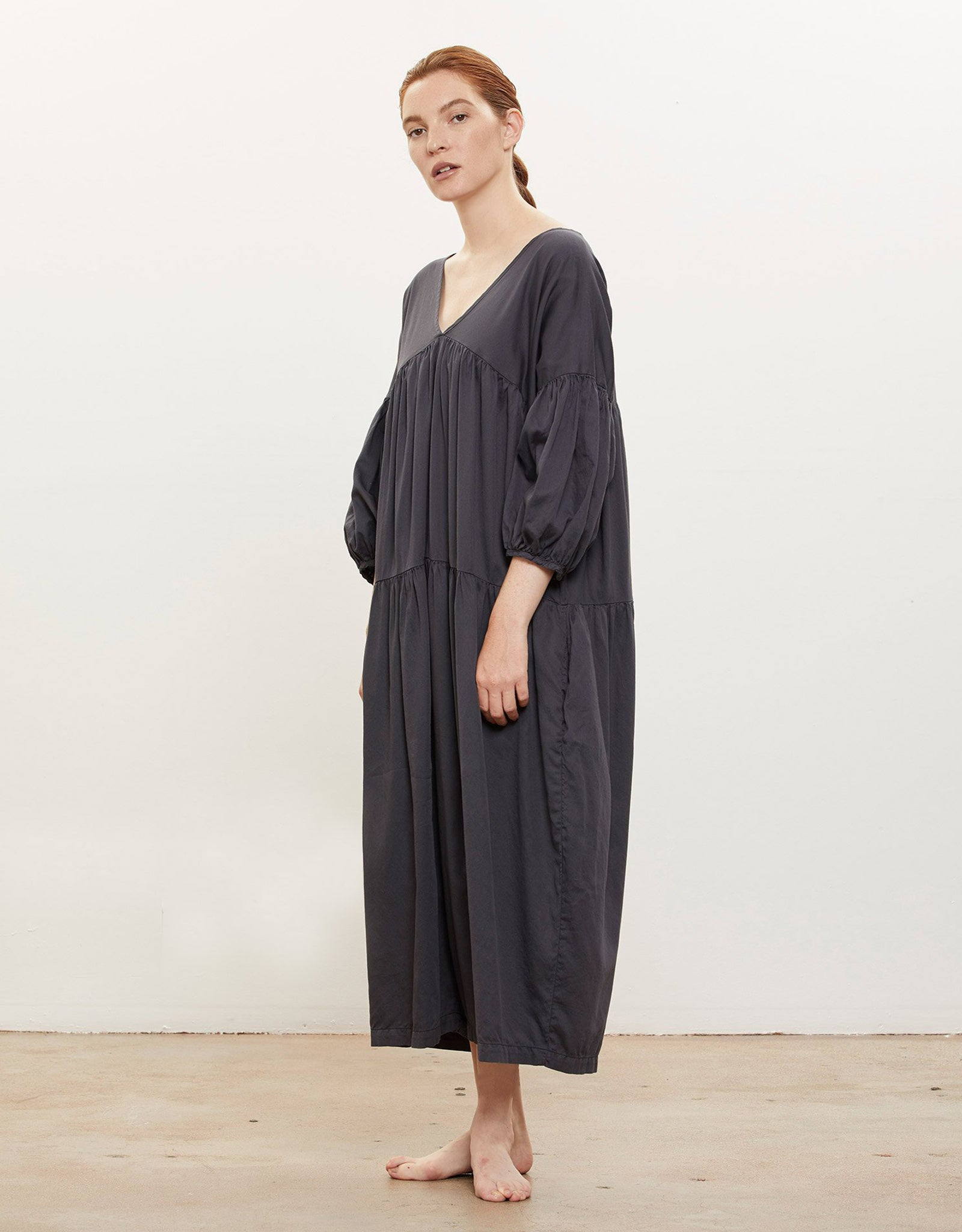 Model wears Black Crane Puff Jumpsuitin Faded Black, side. Available at FAWN Toronto.