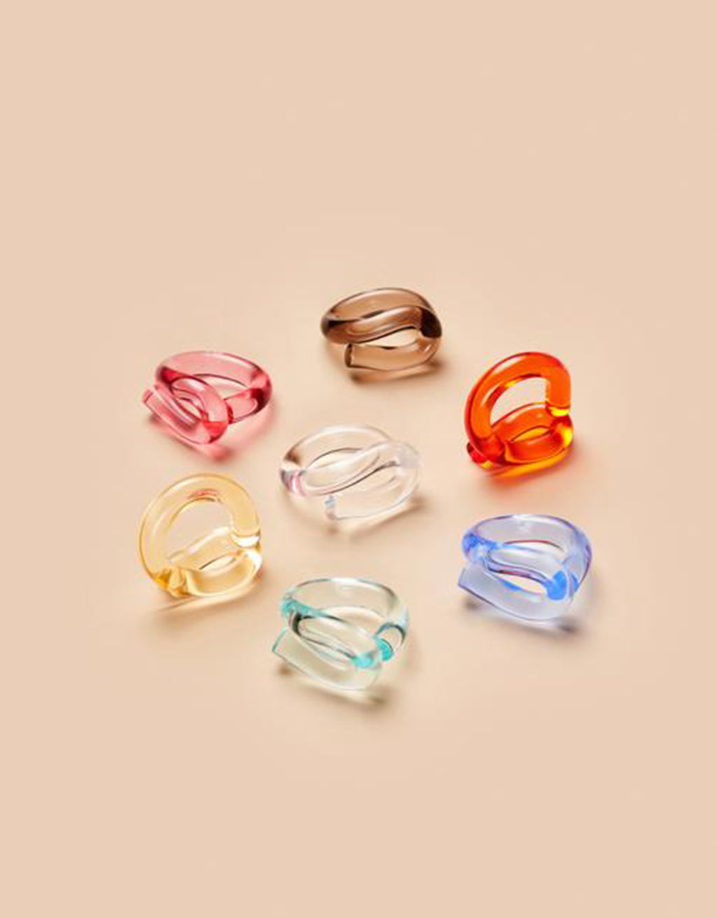 Colourful Loop Rings by Corey Moranis on soft pink background. Available at FAWN Toronto.