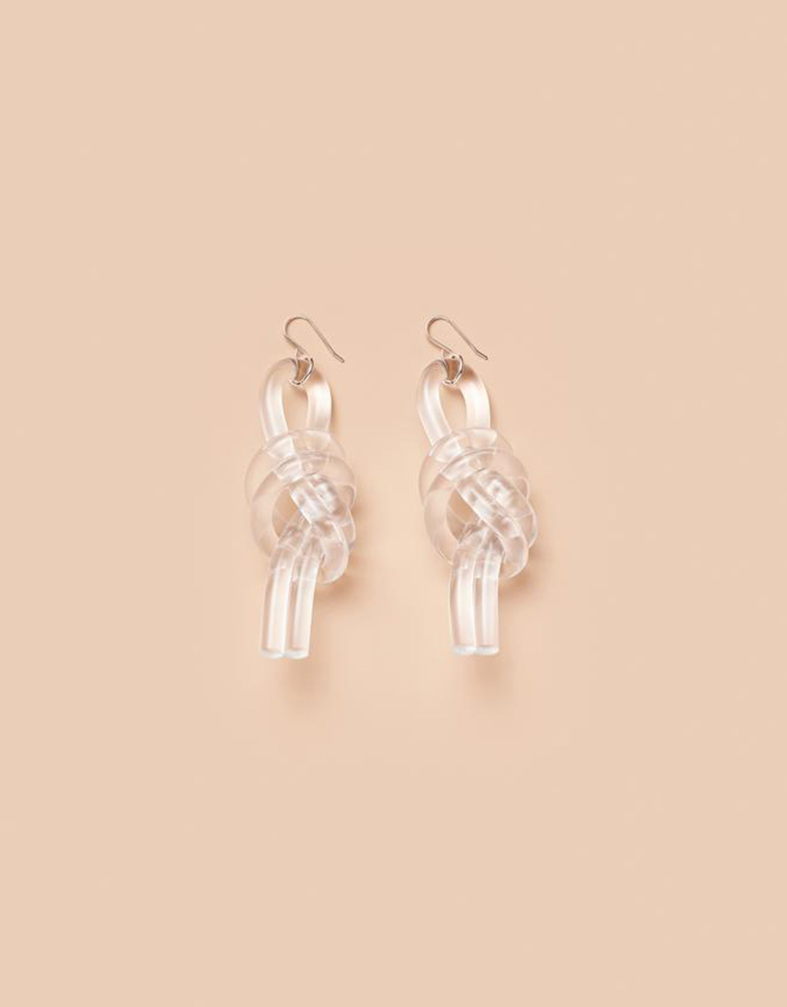 Transparent Double Knot Earrings by Corey Moranis on soft pink background. Available at FAWN Toronto.