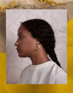 Load image into Gallery viewer, ORA-C brass and silver Jordan Earrings on model with delicate crumpled paper background. Available at FAWN Toronto.