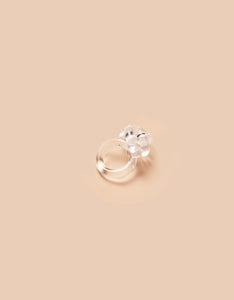 Clear Knot Ring by Corey Moranis on soft pink background. Available at FAWN Toronto.