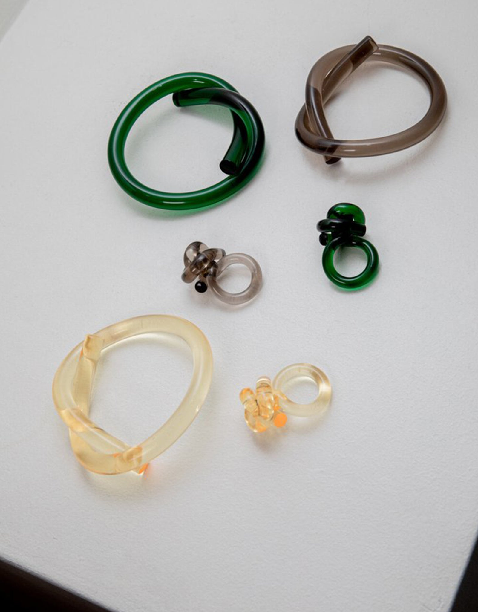 Flatlay of Green, Yellow, and Smoke Knot Rings and Pretzel Bracelets by Corey Moranis. Available at FAWN Toronto.