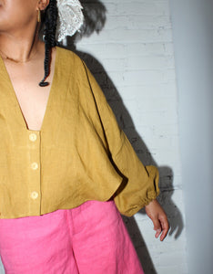 Model wears Nancy Stella Soto V-Neck Cropped Shirt in Ochre, sleeve detail. Available at FAWN Toronto.