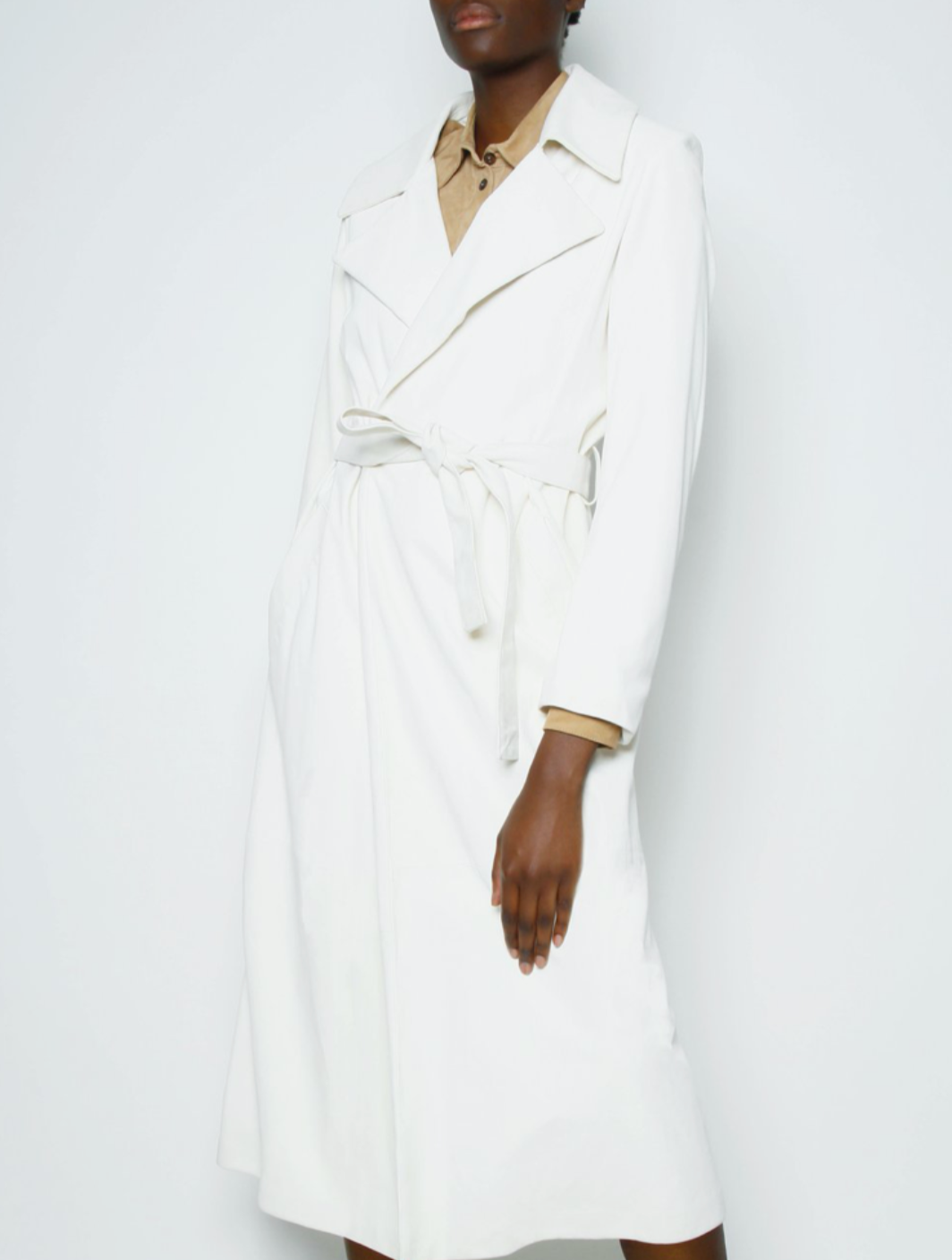 Model wearing leather white trench coat