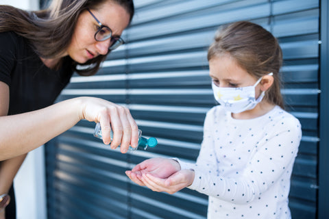 Mom giving daughter hand sanitizer