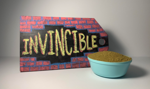 """Product image depicting a heaping bowl of Red Vein Thai Kratom Powder sitting in front of a small sign that reads """"Invincible!"""""""
