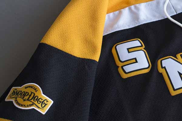 SNOOP DOGG 'STEELTOWN G-PUCK' hockey jersey in black, gold, and white arm patch close-up