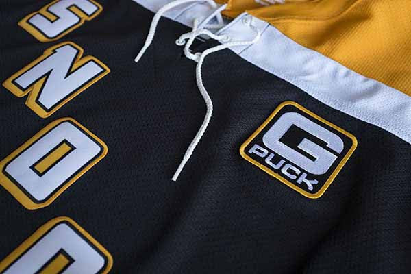 SNOOP DOGG 'STEELTOWN G-PUCK' hockey jersey in black, gold, and white chest patch close-up