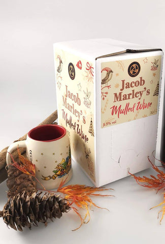 Image shows a photo of a white box of Jacob Marley Mulled Wine, a Christmassy mug, a pine cone and some orange leaves set on an off-white background.