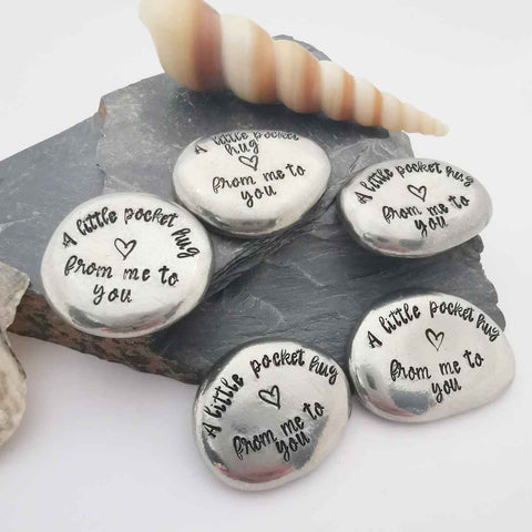 Image shows a collection of hand-stamped pewter pocket hugs (stamped text says: a little pocket hug from me to you) arranged on 2 pieces of grey slate, with a sea-shell at the back.