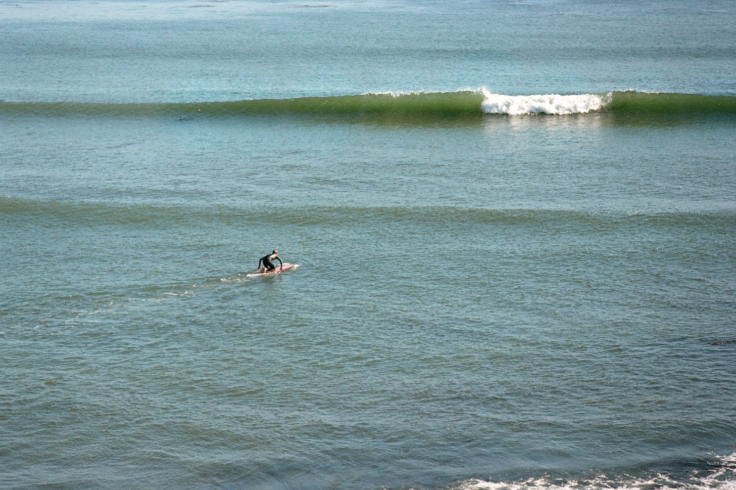 Surfer in the lineup by Ryan Tatar