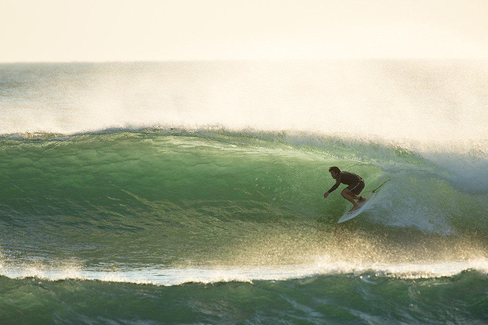 Photo of Jared Mell pulling into a backlit barrel in Costa Rica