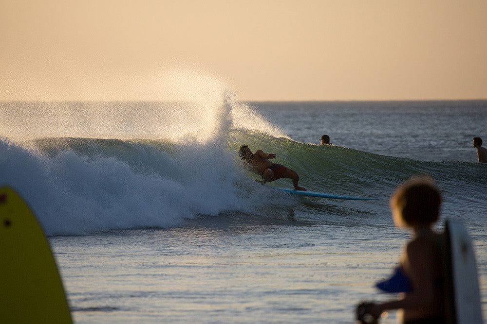 Photo of Jared Mell getting a layback barrel on a longboard in Costa Rica