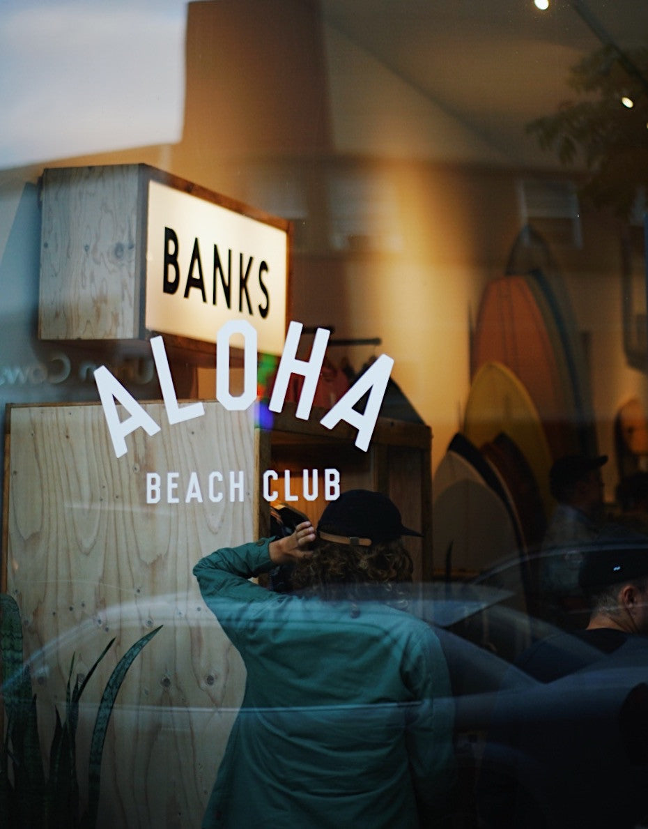 Front window of Aloha Beach Club with Banks Journal logo in the background