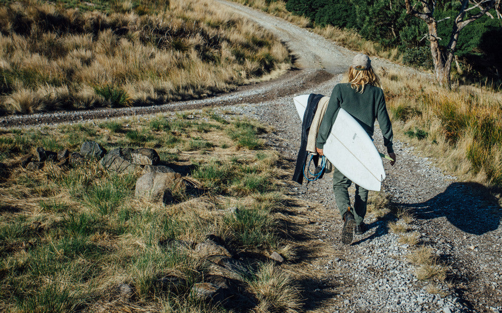 Jasson Salisbury walking back from a surf in Tasmania