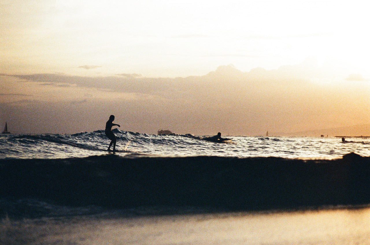 Sunset surfing at Waikiki by Dane Peterson