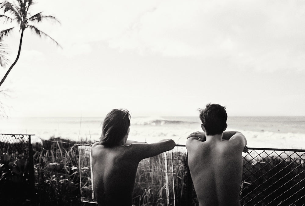 Black and white photo by John Hook of two groms watching Pipeline