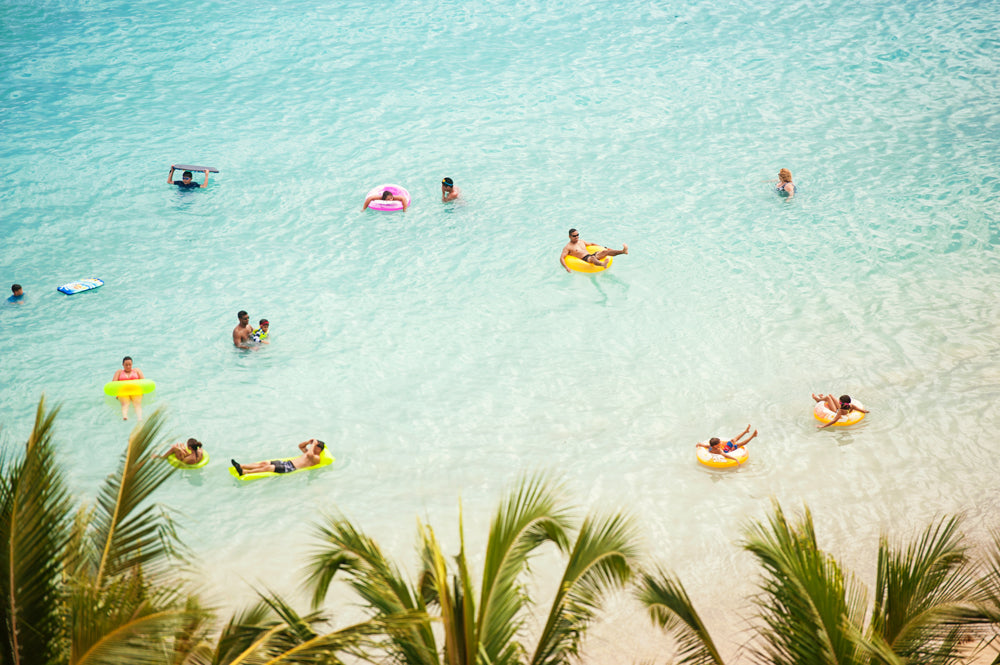 tourists floating around at Waikiki Beach by photographer John Hook