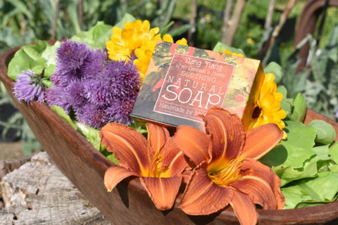 natural soap ylang ylang with honey and oatmeal in the midst of flowers