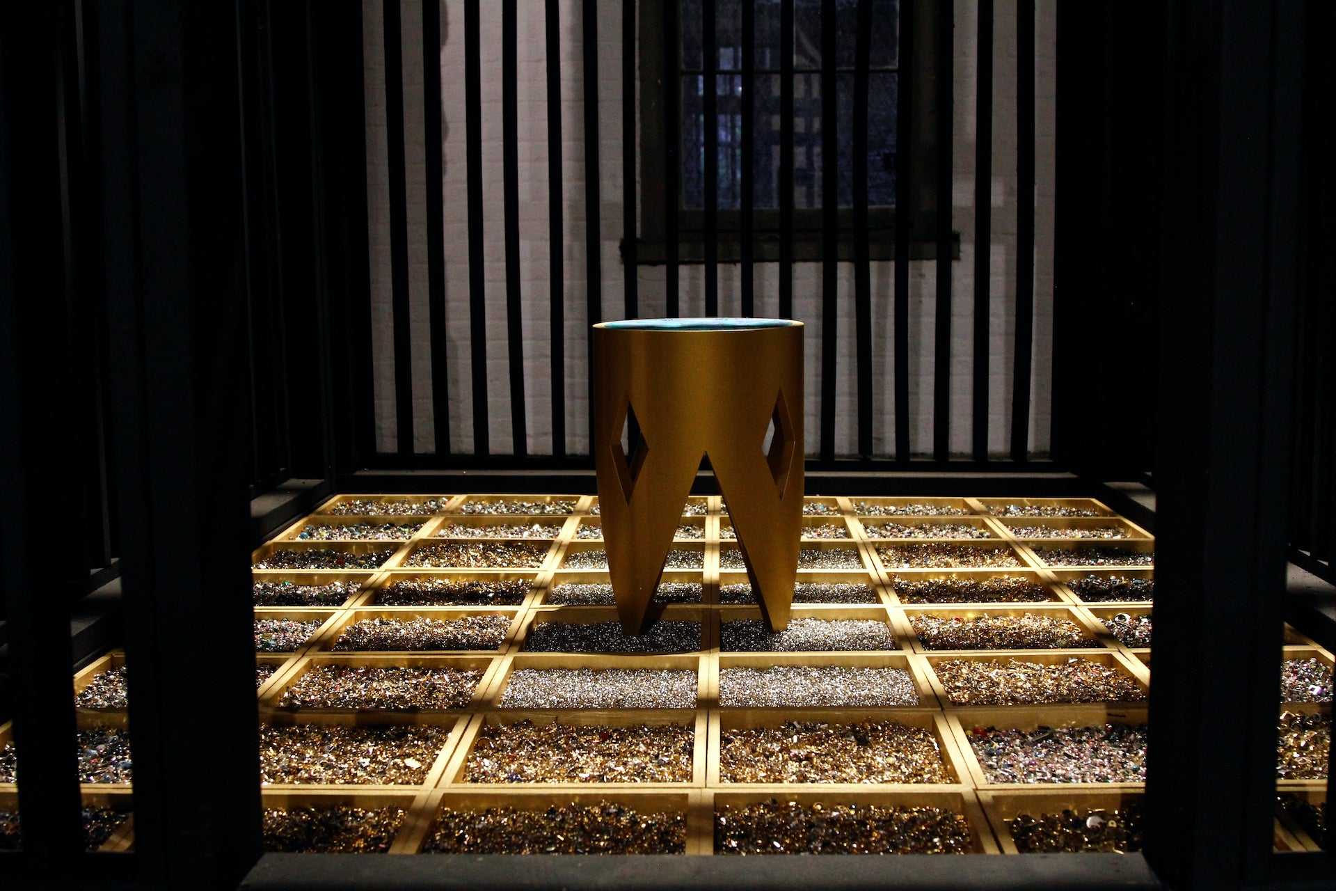 Isolation, a constructed jail cell, features a single stool to represent solitary confinement. The floor is composed of boxes and metal trinkets, signatures of the Ladds' practice. Image © Simon Courchel / The Invisible Dog