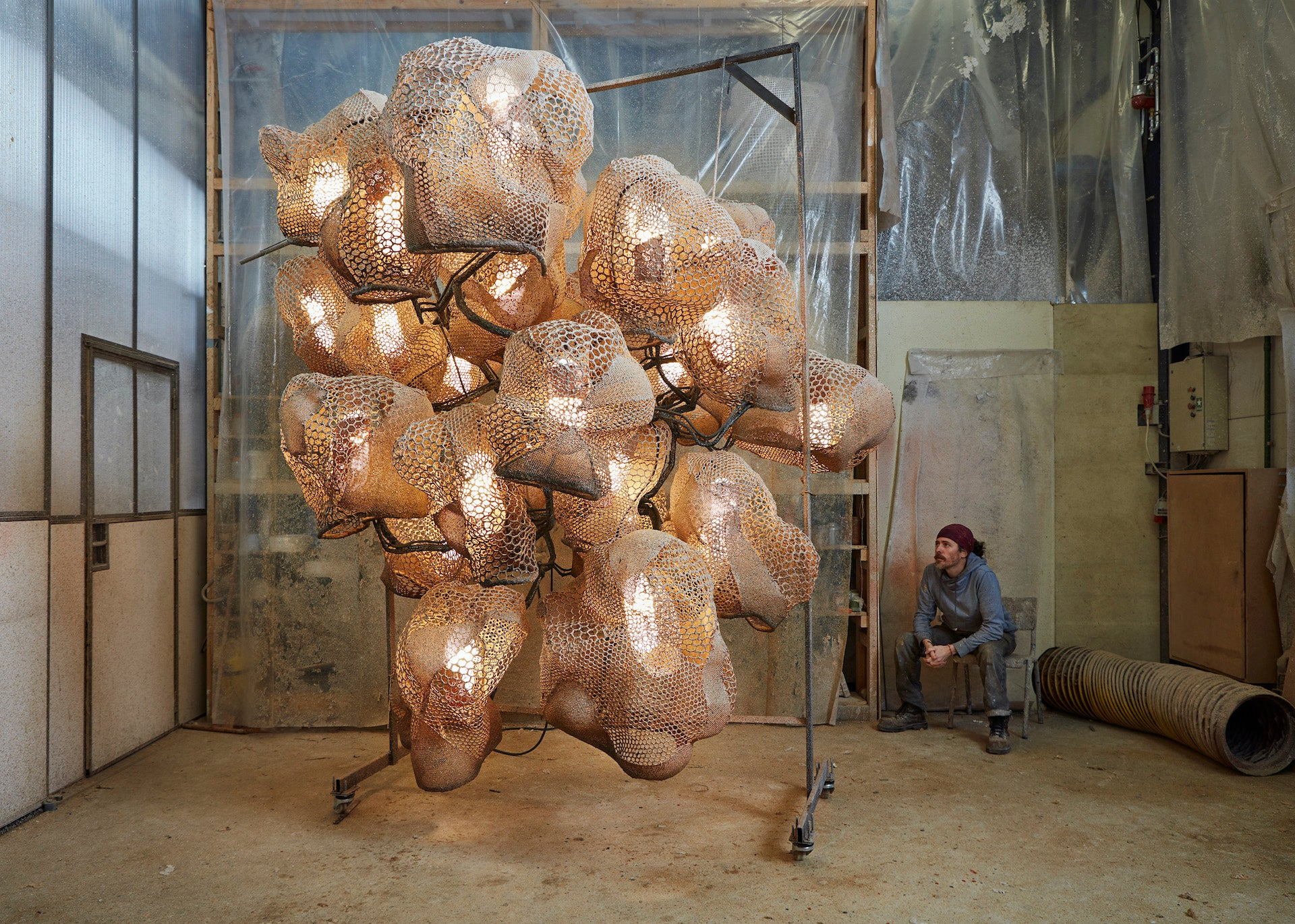 Carbonell sits beside his Big Round Chandelier 1, 2018. Photo © Carpenters Workshop Gallery