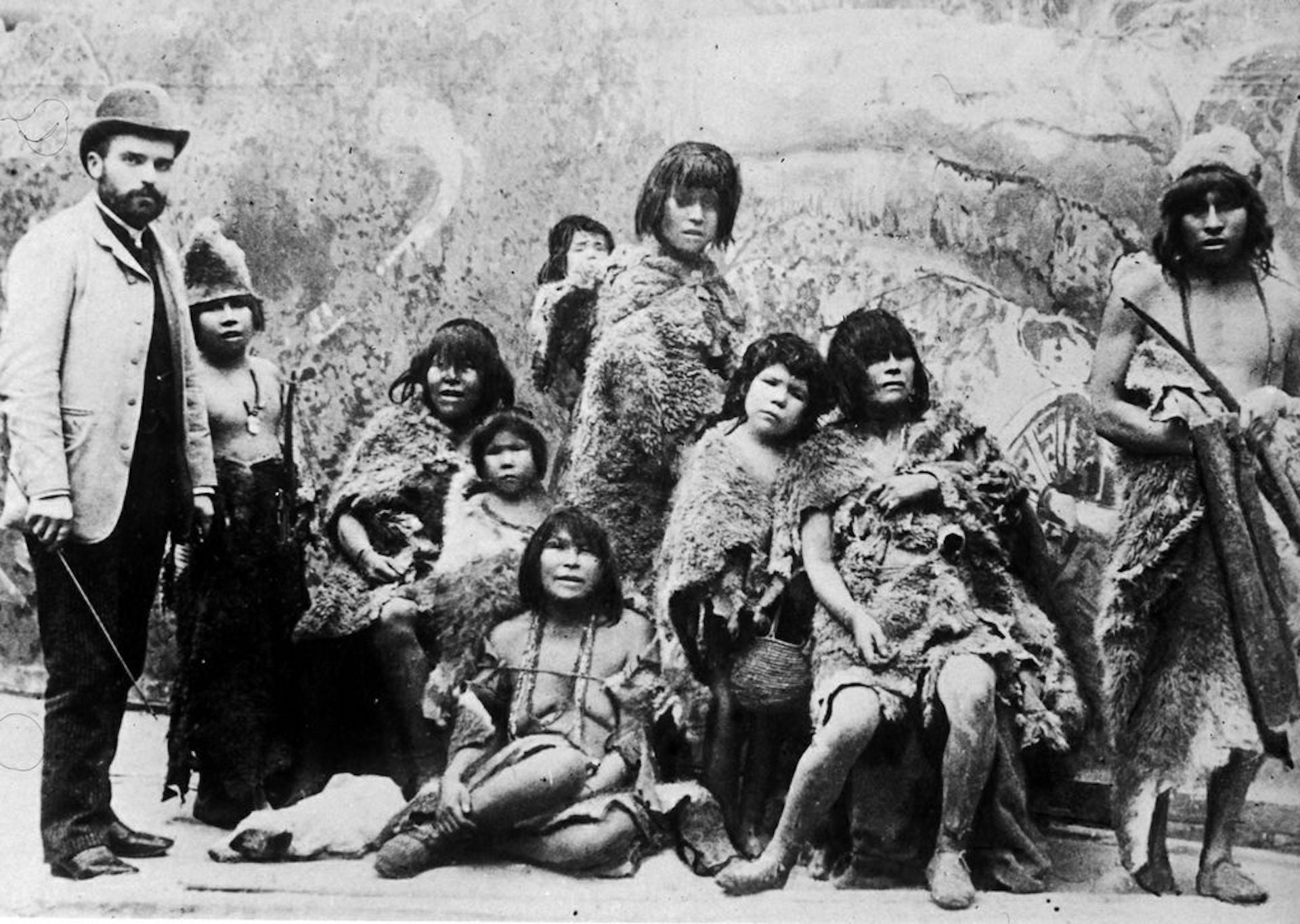 """""""In 1889, Belgian Maurice Maitre kidnapped a family of Selk'nam people, whom he took in chains to be exhibited in Europe like animals. Of the 11, two died on the trip. In Paris, they were presented behind bars as alleged cannibals; every afternoon the public threw raw horse meat at them. They were kept dirty, so that they had the appearance of savages. Given the inhumane conditions of the exhibition, the Missionary Society began demanding the family's release. So Maitre took them to Brussels, where they were imprisoned and then deported to England. From there the family embarked for Tierra del Fuego. Of the 11, six made it home according to Chilean authorities."""" Photo © Adolfo Kwasny c. 1889, in the public domain"""
