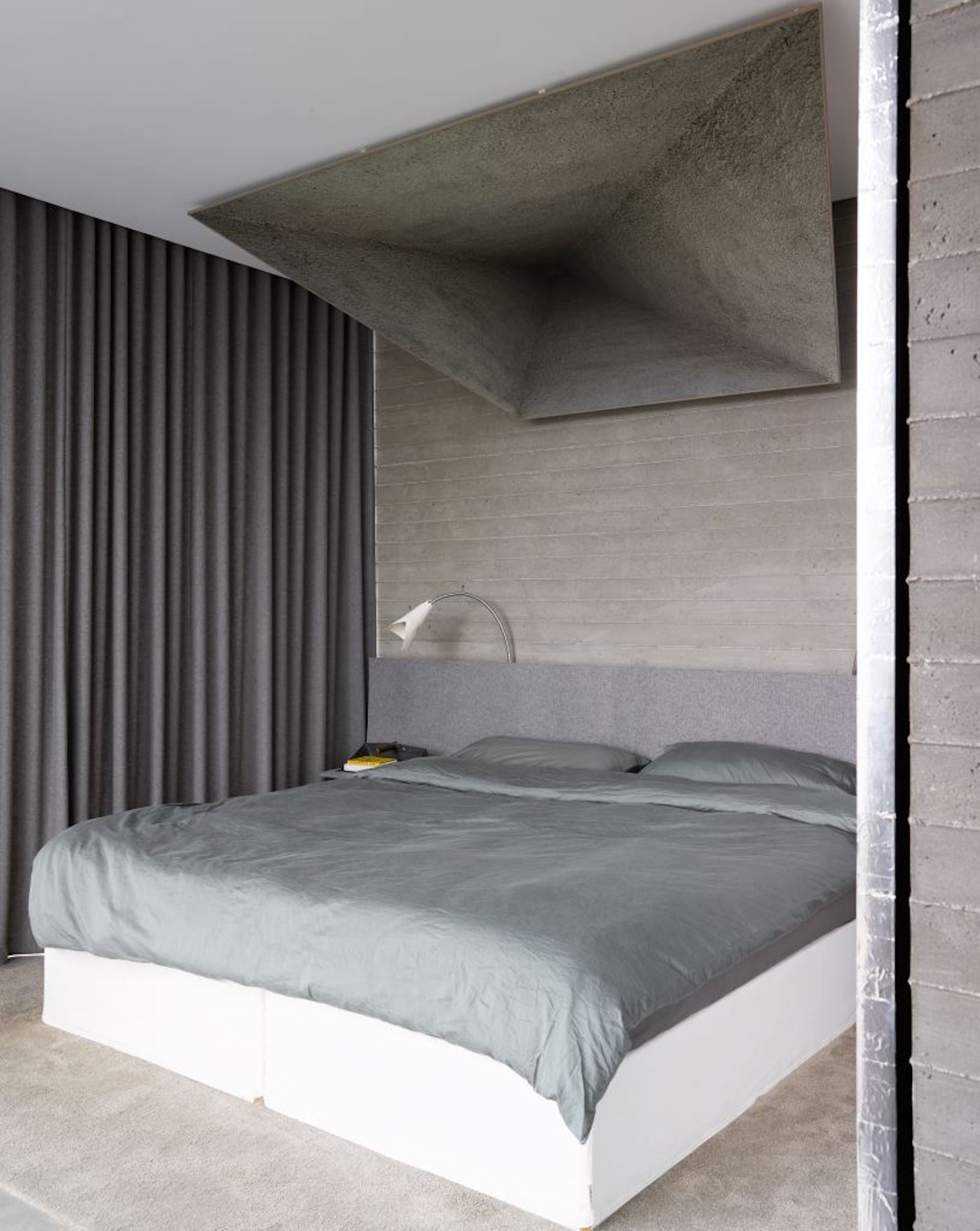 In the bedroom, a custom felt headboard with lamps by wHY. Photo © Richard Powers
