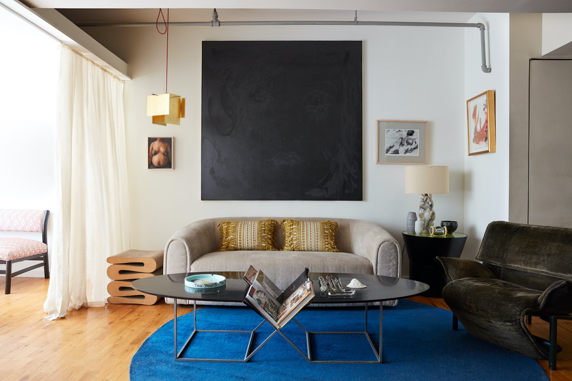 In Lewis's own home, the living space is partitioned by a West Elm sofa, set beneath a painting by Ricardo Gonzalez. The coffee table is custom made by Anthony Whitfield; armchair by Vico Magistretti for Cassina; Wiggle Stool by Frank Gehry; 24 Karat Blau pendant light by Axel Schultes for Ingo Maurer. Photo © David A. Land