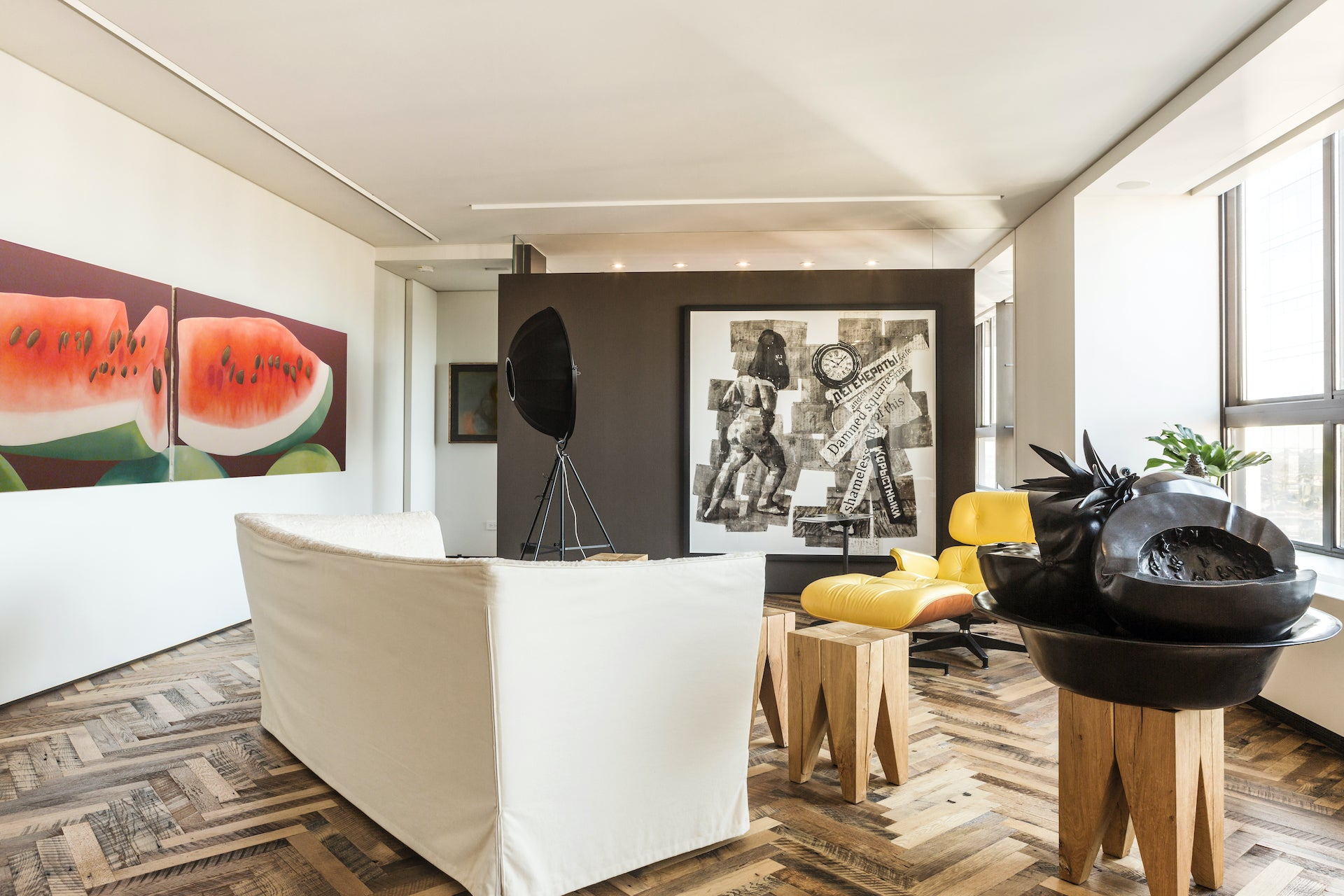 From this view, a dark tobacco wall divides the room while still letting in light. The collage is by William Kentridge; banana-colored lounge chair by Charles and Ray Eames; diptych watermelon painting and bronze fruit bowl sculpture by Ana Mercedes Hoyos. Photo © Pratya Jankong