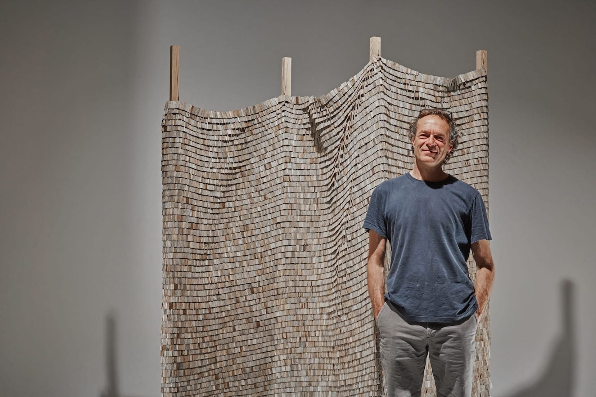 Wycliffe Stutchbury alongside his Gayles Farm 5, 2020; composed of discarded oak fencing on cotton. Photo © Sarah Myerscough Gallery