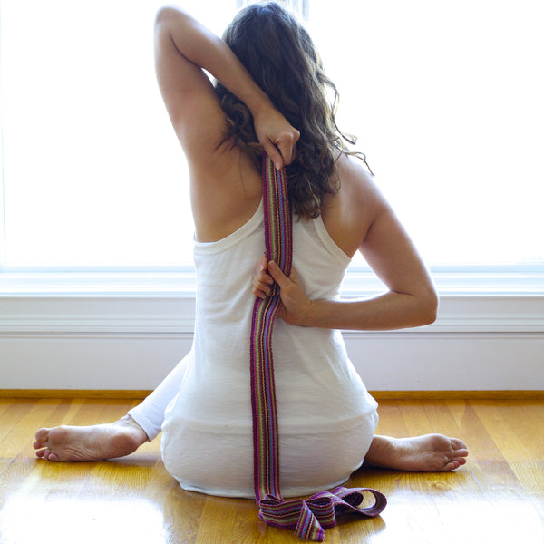 hand dyed and handwoven yoga strap being used by student of yoga