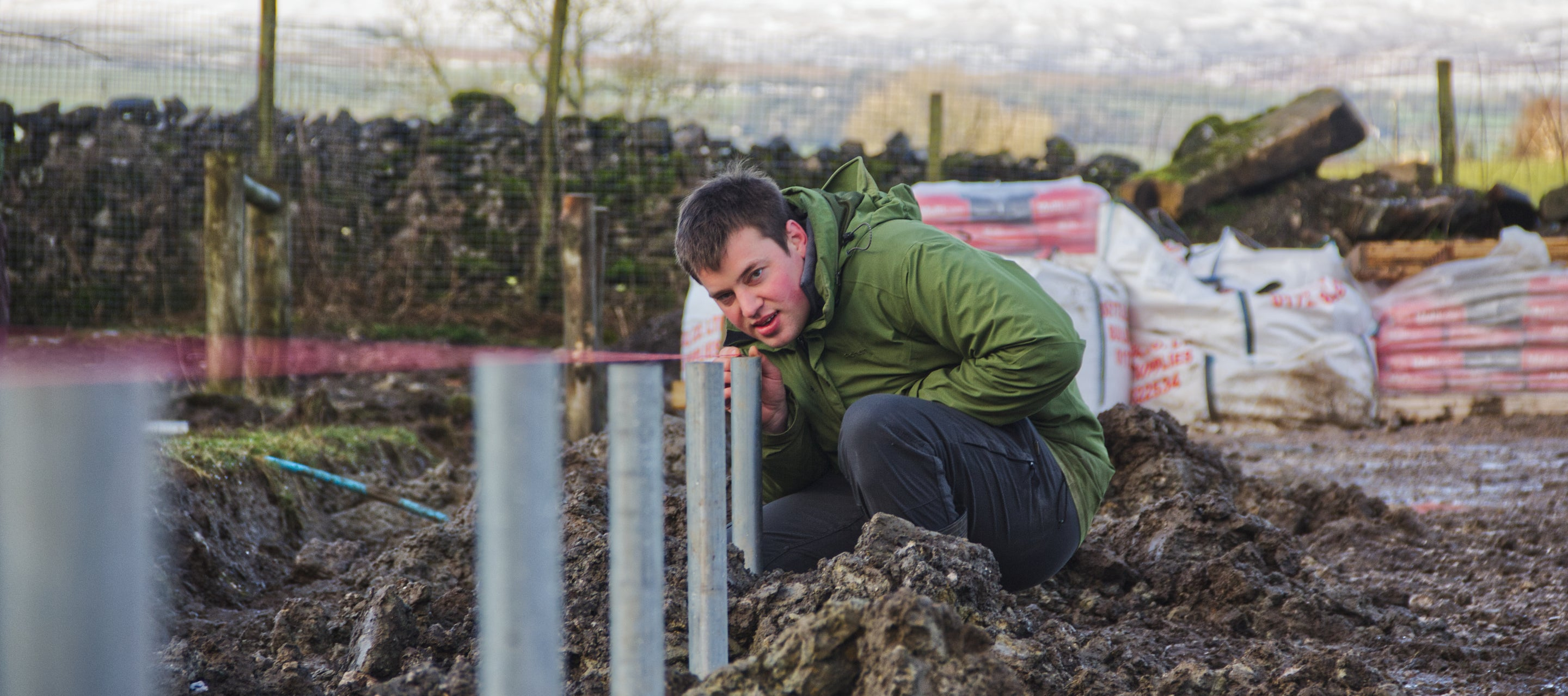 Jimmie draws a line down the edge of what will be his new polytunnel