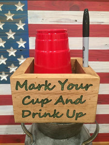 Plastic party cup holder made from solid wood with epoxy inlayed letter that say mark your cup and drink up