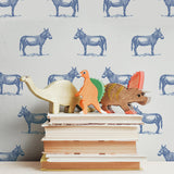 illustrated blue donkey on white background wallpaper pattern behind stack of books peel and stick