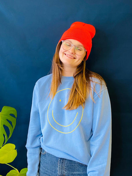 Blue smiley face sweatshirt by Mobak available at Local Assembly