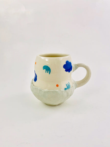Blue and white ceramic mug with blue and orange shapes on it by Coco Spadoni available at Local Assembly