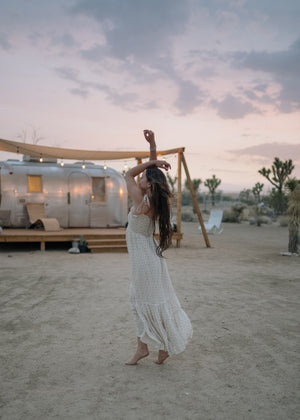barefoot woman dancing in the desert by her camper