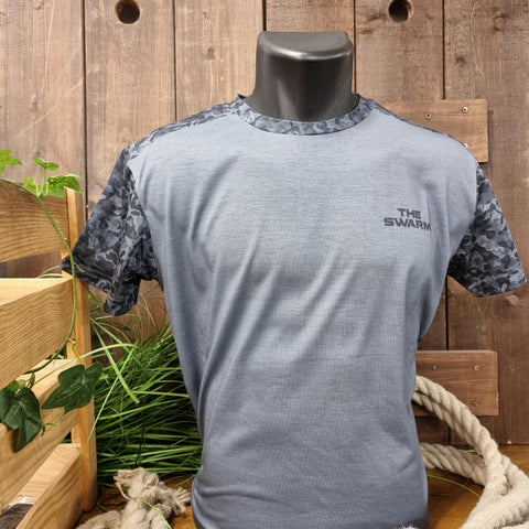 A grey t-shirt with a dark and light grey camo style print across the shoulders and sleeves