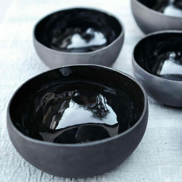 a set of black ceramic bowls