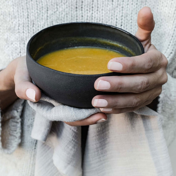 black ceramic bowl with pumpkin soup