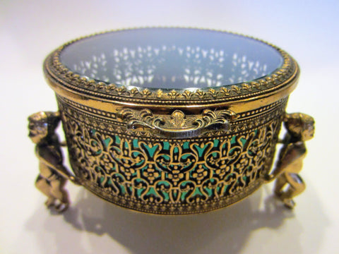 A Brass Jewelry Box Beveled Glass Lid Footed Decorated Putti Heart Filigree